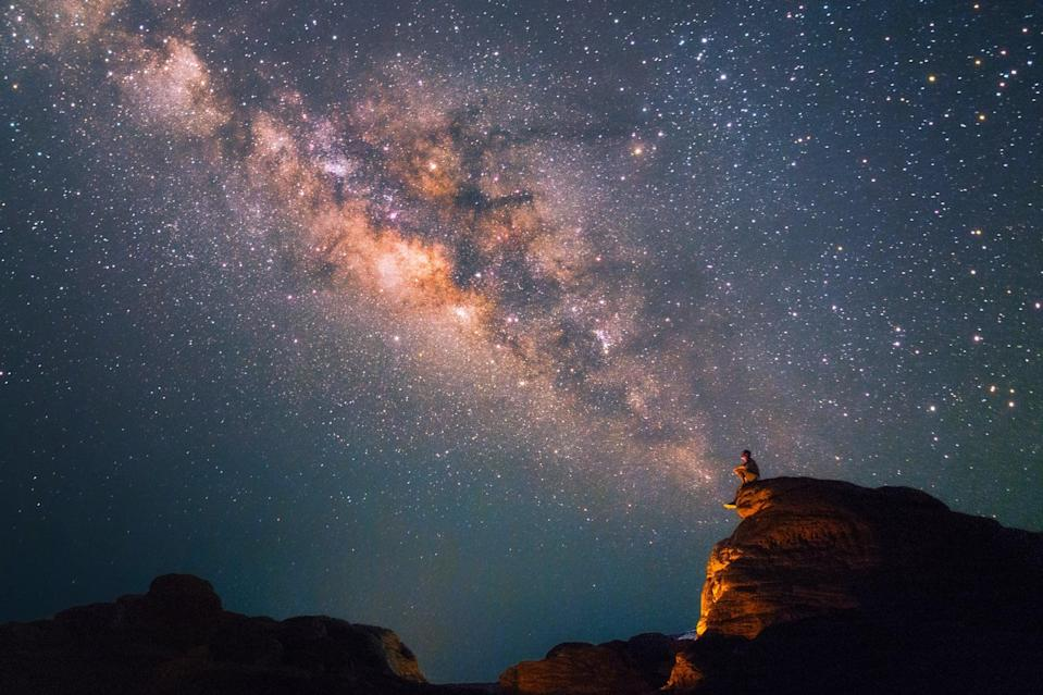 Silhouette man sits on the top of rock looking at the beautiful Milky Way Stars at the Grand Canyon of Thailand (Sam Phan Bok)