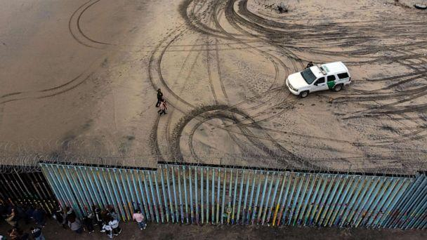 PHOTO: An aerial view of migrants who form part of the Central American migrant caravan being detained and escorted by a border patrol agent after crossing the U.S.-Mexico border fence in Playas de Tijuana, Baja California state, Mexico, Dec. 9, 2018. (Guillermo Arias/AFP/Getty Images, FILE)