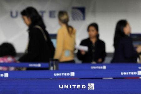 FILE PHOTO: Customers of United wait in line to check in at Newark International airport in New Jersey