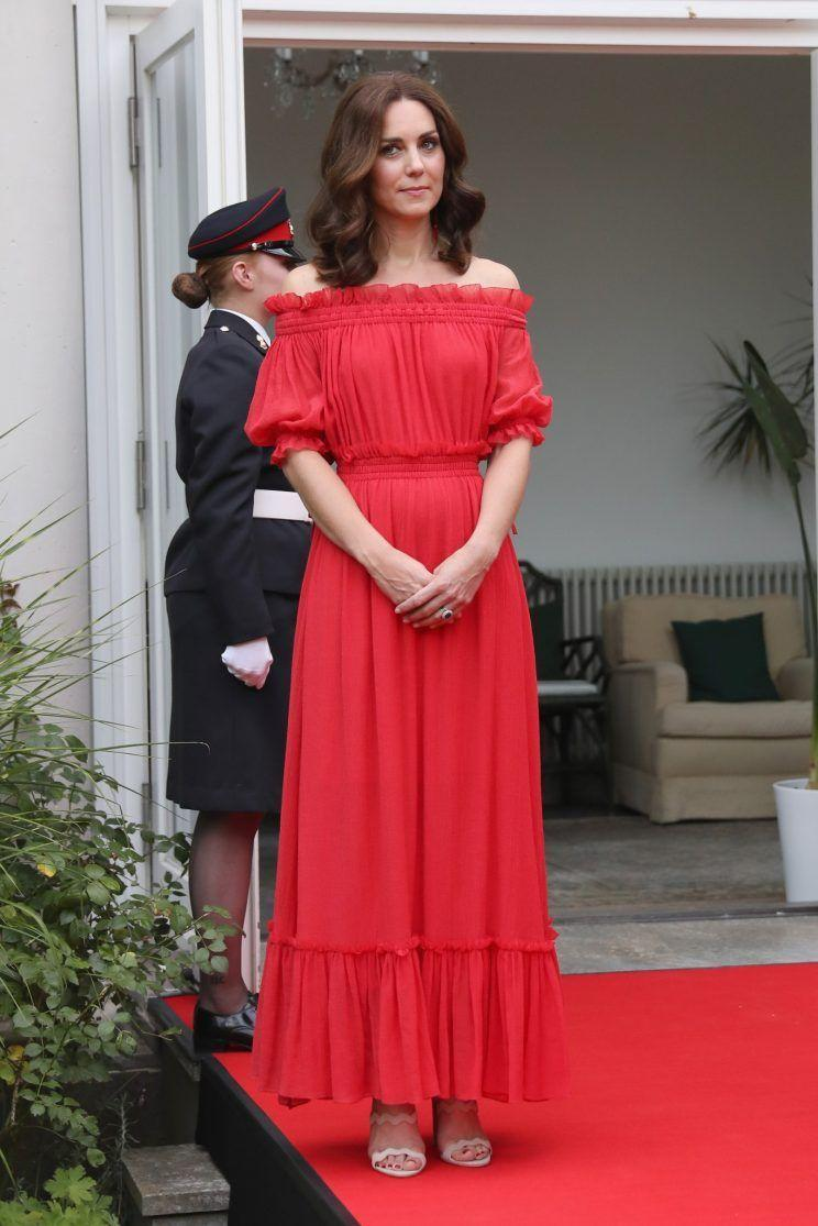 <p>Kate was a lady in red at a Berlin garden party in an off-the-shoulder Alexander McQueen dress. The Bardot-style gown was paired with a pair of scalloped sandals by Prada.<br><i>[Photo: PA]</i> </p>