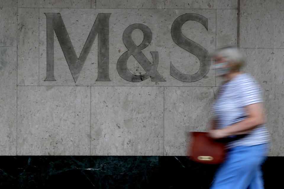 A woman passes the sign on a branch of Marks and Spencer in London, Tuesday, Aug. 18, 2020. Marks and Spencer has said it will cut 7,000 jobs over the next three months as the UK retailer overhauls its business in the latest sign of how the coronavirus pandemic has disrupted the high street. (AP Photo/Kirsty Wigglesworth)