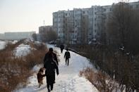 People walk next to residential buildings in the coal city of Hegang