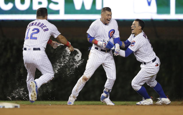 Chicago Cubs' Albert Almora Jr., center, celebrates with teammates Kyle Schwarber (12) and Javier Baez after hitting his game winning RBI single off Los Angeles Dodgers relief pitcher Brock Stewart, during the 10th inning of a baseball game Tuesday, June 19, 2018, in Chicago. Kris Bryant scored in the Cubs 2-1 win. (AP Photo/Charles Rex Arbogast)