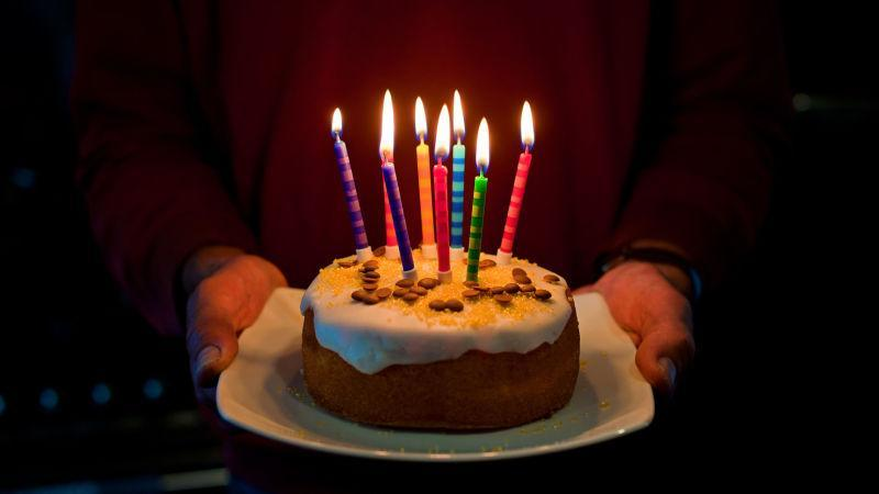 Hands holding out a birthday cake with candles lit