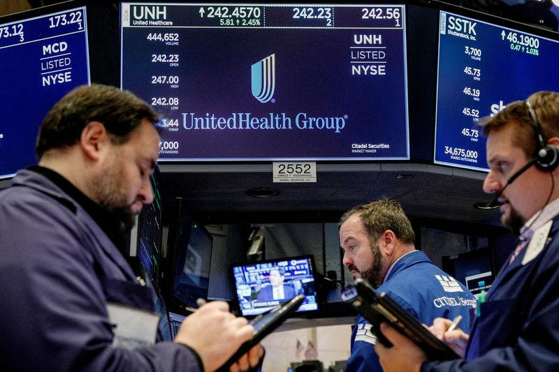 FILE PHOTO: Traders work at the post where UnitedHealth Group is traded on the floor of the New York Stock Exchange (NYSE) in New York, U.S., January 31, 2018. REUTERS/Brendan McDermid/File Photo