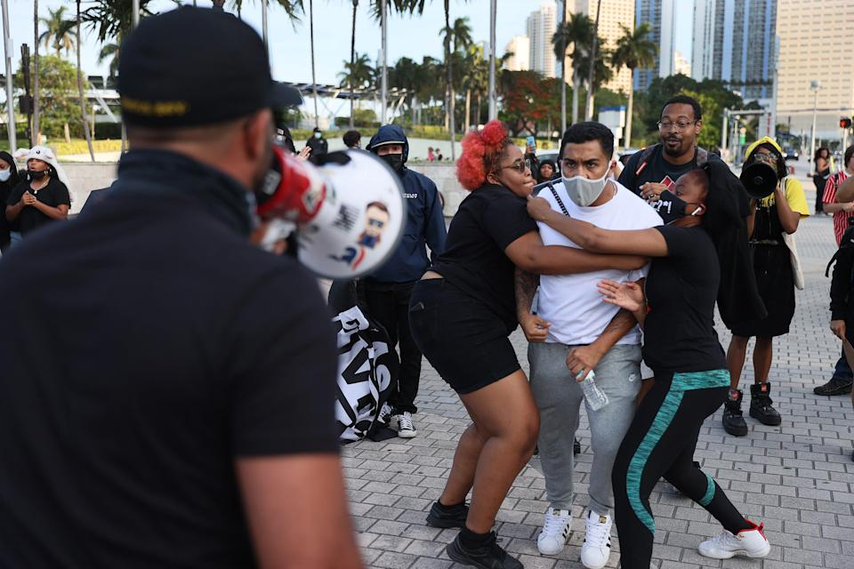 A man is held back as Enrique Tarrio, back to camera, leader of the Proud Boys, uses a megaphone during a counterprotest in Miami at the commemoration of the one-year anniversary of the killing of George Floyd on May 25. Tarrio led a group expressing support of police officers. Floyd's murder by Minneapolis police officer Derek Chauvin led to global protests.