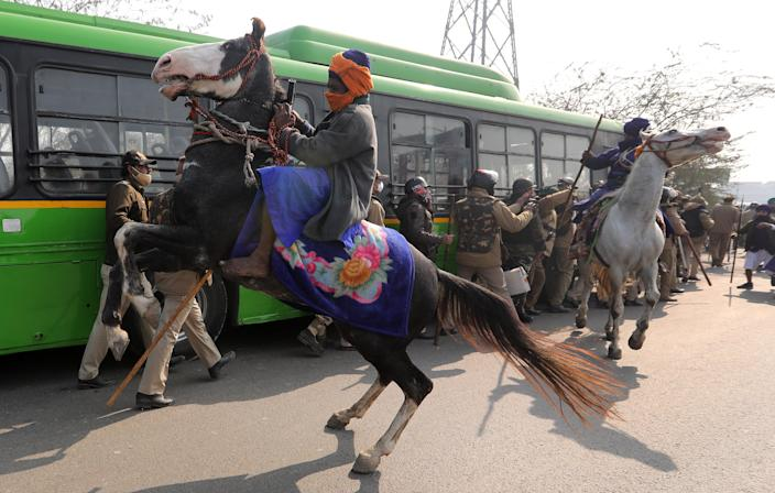 Men belonging to an armed Sikh order clash with police personnel as people take part in a 'parallel parade' on tractors and trolleys, during the ongoing farmers protest against new farm lawsEPA