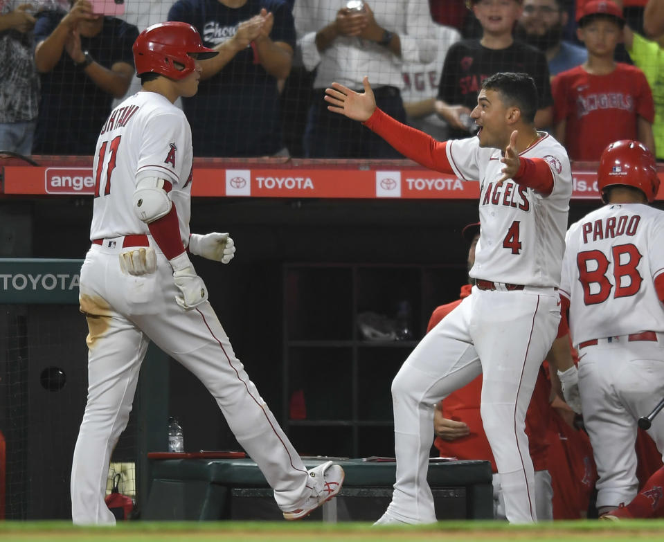 Los Angeles Angels' Shohei Ohtani is congratulated by Josd Iglesias after hitting a three-run home run during the fourth inning of a baseball game against the Colorado Rockies on Wednesday, July 28, 2021, in Anaheim, Calif. (AP Photo/John McCoy)