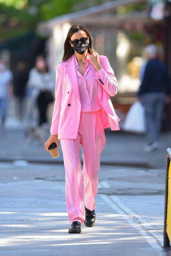 """<p>The model stepped out in Manhattan wearing a pink suit and shirt from Hugo Boss to grab coffee. Shayk colour-drenched with a matching By Far handbag, and toughened up the look with Dr Martens boots. </p><p><a class=""""link rapid-noclick-resp"""" href=""""https://go.redirectingat.com?id=127X1599956&url=https%3A%2F%2Fwww.selfridges.com%2FGB%2Fen%2Fcat%2Fby-far-cush-grained-leather-shoulder-bag_R03752724%2F&sref=https%3A%2F%2Fwww.elle.com%2Fuk%2Ffashion%2Fcelebrity-style%2Fg34359706%2Firina-shayk-style-file%2F"""" rel=""""nofollow noopener"""" target=""""_blank"""" data-ylk=""""slk:SHOP IRINA'S BAG HERE"""">SHOP IRINA'S BAG HERE</a></p>"""