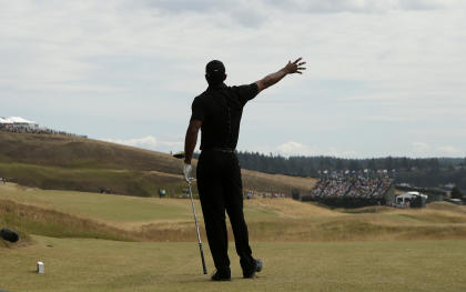 Tiger Woods watches his tee shot on the eighth hole veer right at Chambers Bay. (AP)