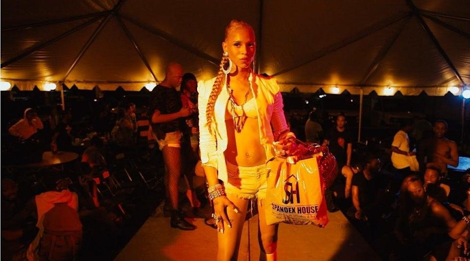 A woman stands on a raised runway at a kiki event