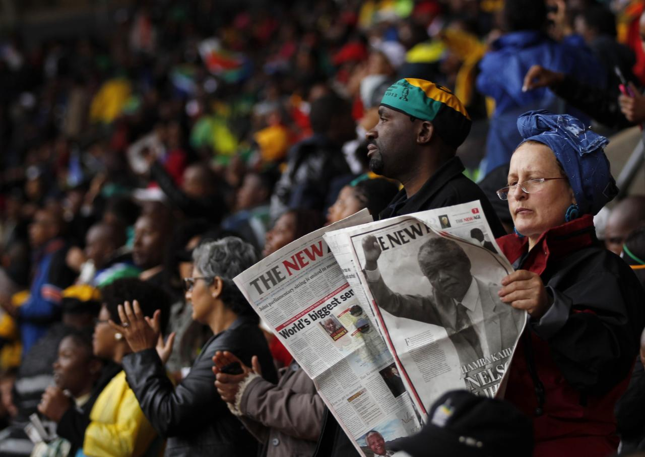 A woman reads the papers at the First National Bank (FNB) Stadium, also known as Soccer City, during the national memorial service for former South African President Nelson Mandela in Johannesburg December 10, 2013. World leaders from U.S. President Barack Obama to Cuba's Raul Castro joined thousands of South Africans to honour Nelson Mandela on Tuesday in a memorial that will celebrate his gift for uniting enemies across political and racial divides. REUTERS/Siphiwe Sibeko (SOUTH AFRICAPOLITICS - Tags: POLITICS OBITUARY)