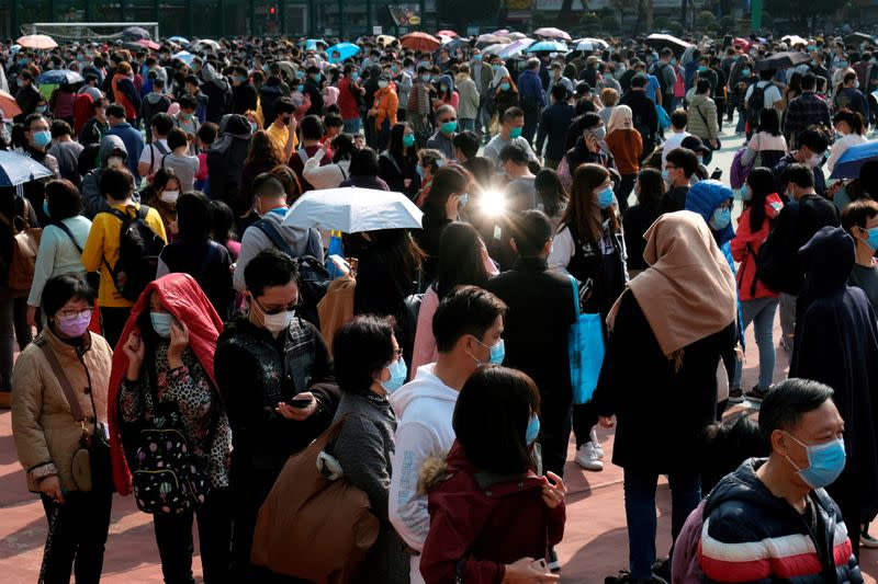 FILE PHOTO: Customers queue up to buy masks amid an outbreak of a new coronavirus, in Hong Kong