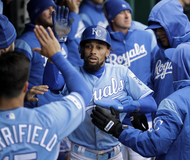 Kansas City Royals Billy Hamilton celebrates in the dugout after scoring on a double by Adalberto Mondesi during the third inning of a baseball game against the Chicago White Sox Saturday, March 30, 2019, in Kansas City, Mo. (AP Photo/Charlie Riedel)