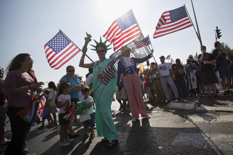 """FILE - In this Oct. 1, 2015 file photo, evangelical Christians from various countries wave American flags in Jerusalem. An evangelical broadcaster who boasted of miraculously securing a TV license in Israel now risks being taken off the air over suspicions of trying to convert Jews to Christianity. The controversy over """"GOD TV"""" has put both Israel and its evangelical Christian allies in an awkward position. Evangelical Christians, particularly in the United States, are among Israel's strongest supporters. Israel has long welcomed their political and financial support, especially as their influence has risen during the Trump era. (AP Photo/Sebastian Scheiner, File)"""