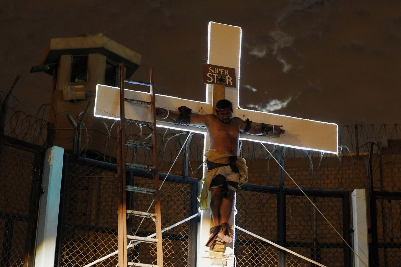 "An inmate depicting Jesus performs the crucifixion scene in the theatre play ""Jesus Christ Superstar"" at Sarita Colonia prison yard, ahead of Holy Week celebrations, in Lima April 15, 2014. The play was held to encourage the inmates in their rehabilitation process, according to the prison's press release. Sarita Colonia's population is made up of 3,113 inmates, out of which 472 are foreigners. Picture taken April 15, 2014. REUTERS/Enrique Castro-Mendivil (PERU - Tags: RELIGION CRIME LAW TPX IMAGES OF THE DAY)"