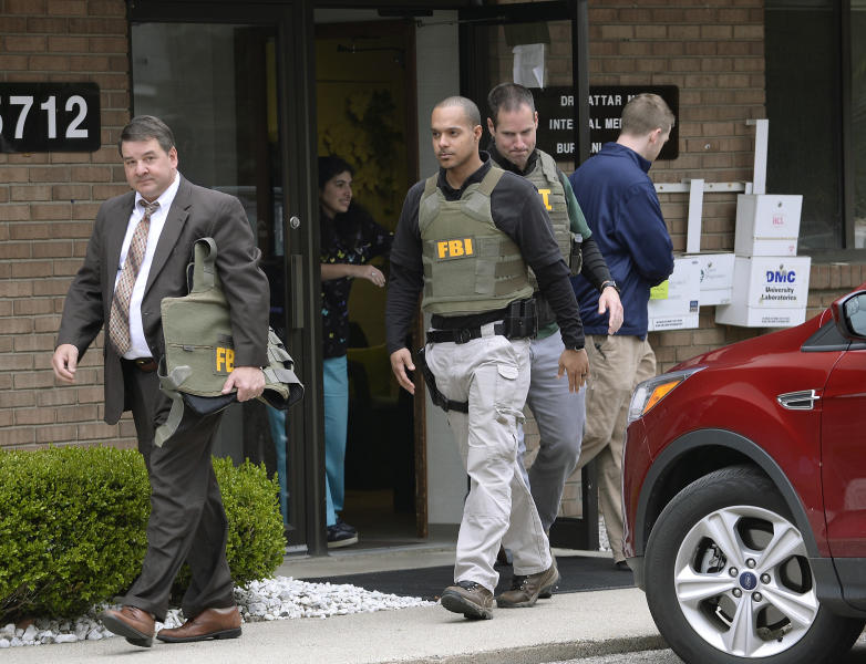 FBI agents leave the office of Dr. Fakhruddin Attar at the Burhani Clinic in Livonia, Mich. Friday, April 21, 2017, after completing a search for documents. The investigation is connected to the case of Dr. Jumana Nagarwala, of Northville, charged with performing genital mutilation on two young girls from Minnesota. (Clarence Tabb Jr. /Detroit News via AP)