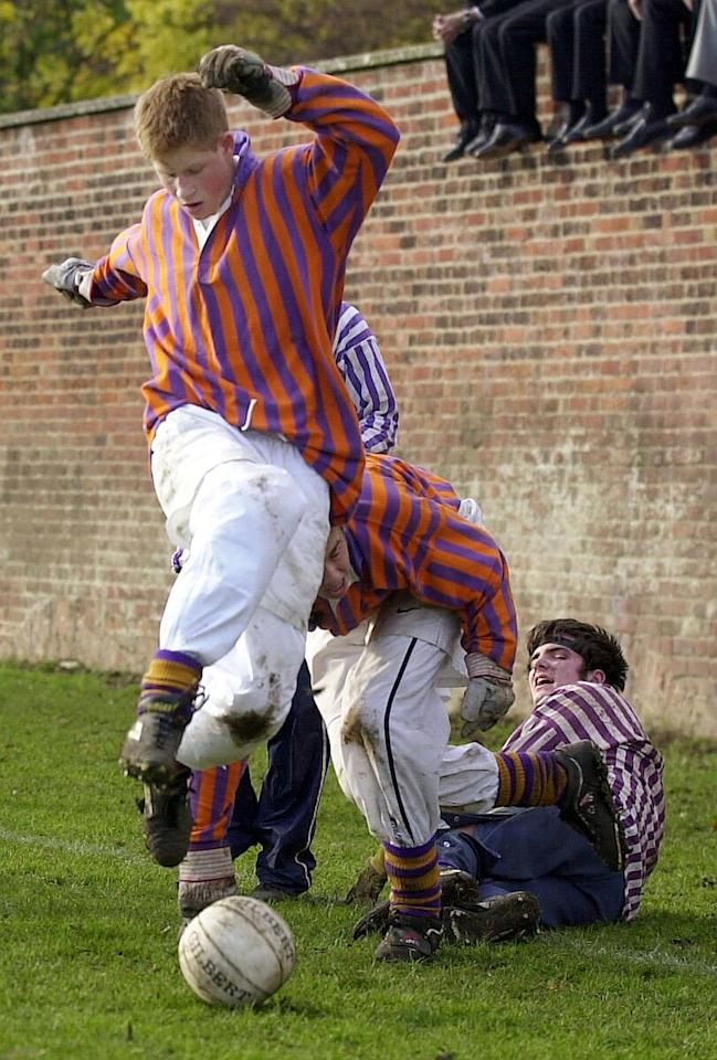 Britain's Prince Harry, 17, clears the loose ball away from the bully during the annual St. Andrew's Day Eton Wall Game, the annual contest of murky rules and no scoring, at Eton College, Berkshire, England Saturday, Nov. 24, 2001. The game, reputedly first played in 1776, pits two teams of 10 in an hour-long battle along a 118-yard wall. The playing area is five yards wide and has goals at either end.  No one has scored in the annual contest since 1909.  (AP Photo/Toby Melville, Pool)