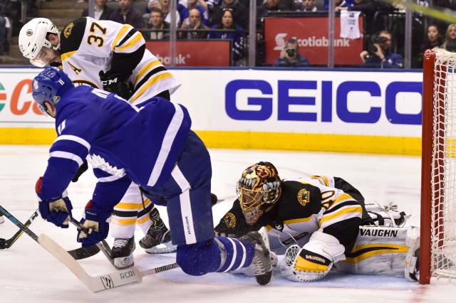 Boston Bruins goaltender Tuukka Rask (40) gets low to watch for the puck as teammate Patrice Bergeron (37) battles Toronto Maple Leafs centre Zach Hyman (11) during the third period of game six of an NHL round one playoff hockey game in Toronto on Monday, April 23, 2018. (Frank Gunn/The Canadian Press via AP)