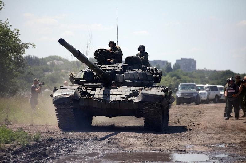 Members of the OSCE Mission control the withdrawal of heavy weapons of pro-Russian separatists near the western Ukrainian city of Donetsk on July 19, 2015