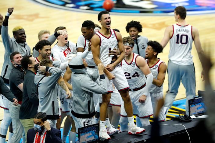 Gonzaga guard Jalen Suggs (1) leaps on a sideline table to celebrate after sinking a three-pointer at the buzzer to defeat UCLA in overtime during the 2021 men's NCAA Tournament national semifinals.