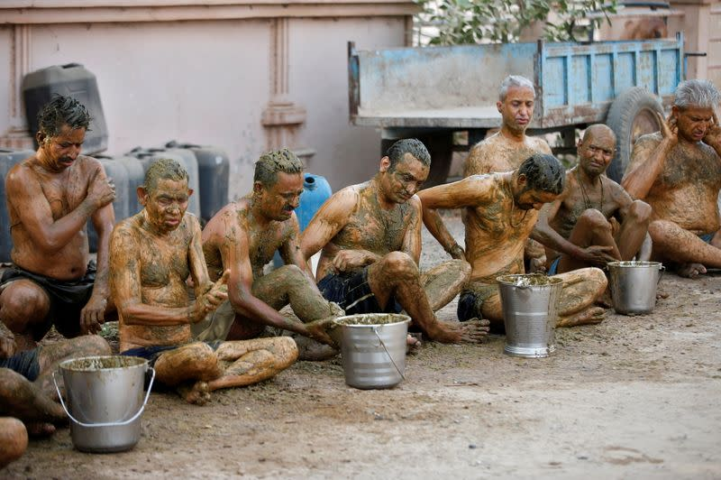 """People apply cow dung on their bodies during """"cow dung therapy"""" on outskirts of Ahmedabad"""
