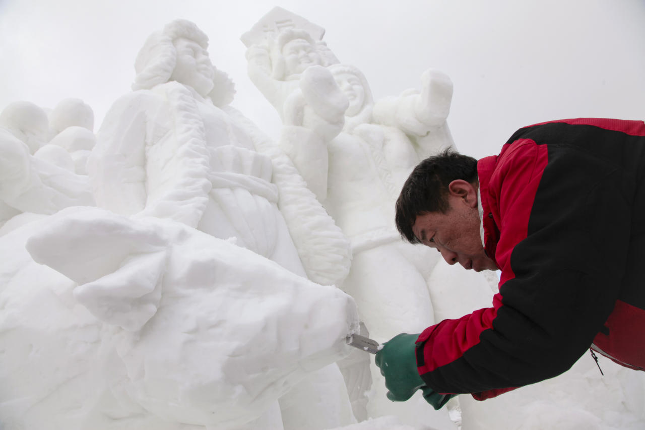 IMAGE DISTRIBUTED FOR THE BRECKENRIDGE RESORT CHAMBER - The captain of Team China, Hongchun Liang carving away snow to make the mouth of a cow on his 12 foot tall, 20-ton sculpture at the outdoor art gallery during the 23rd Annual International Snow Sculpture Championships in Breckenridge, Colo., on Friday, Jan. 25, 2013. Liang is joined with 15 international teams, the sculptures will remain on display through Feb. 3, 2013 (weather permitting). Visit www.gobreck.com for more information. (Nathan Bilow / AP Images for The Breckenridge Resort Chamber)