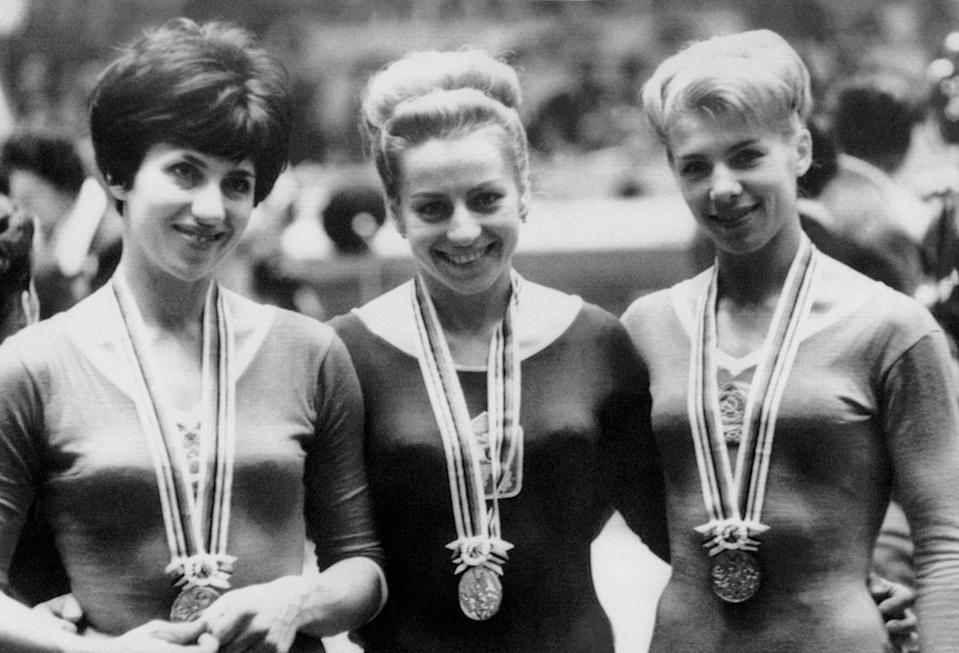 TOKYO, JAPAN - OCTOBER 23:  Czech gymnast Vera Caslavska, winner of the gold medal in the individual beam competition, smiles as she is flanked by silver medalist Tamara Manina (L) and bronze medalist Latissa Latynina, both from the Soviet Union, 23 October 1964 at the Olympic Games in Tokyo.  (Photo credit should read STF/AFP/Getty Images)