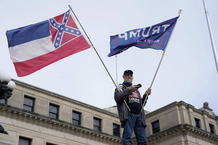 Lee Anglada of Biloxi, stands on the steps of the Mississippi Capitol and waves the retired state flag which incorporated a Confederate battle emblem and a pro-Trump banner during a small protest of the constitutional process to affirm the president-elect's victory in the November election at the Capitol in Jackson, Miss., Wednesday, Jan. 5, 2021. (AP Photo/Rogelio V. Solis)
