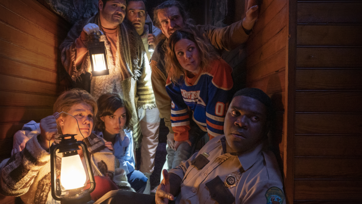 Seven adults, dressed alternatively in winter clothing, hockey jerseys, and ranger uniforms, crowd into a cramped wooden hallway, holding lanterns.