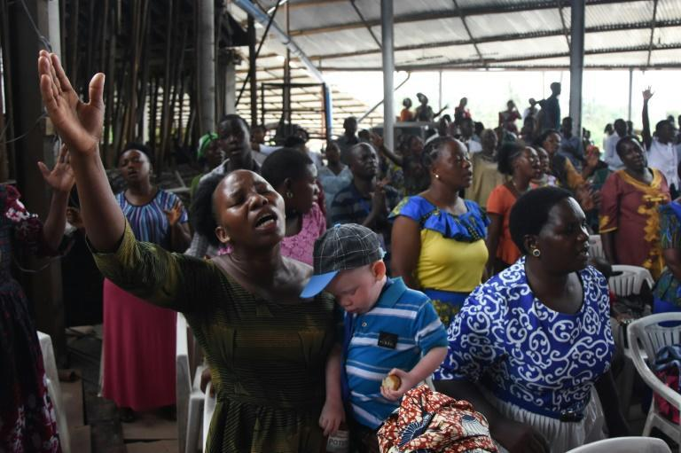 People attend Sunday mass without masks or social distancing at a church in Dar es Salaam