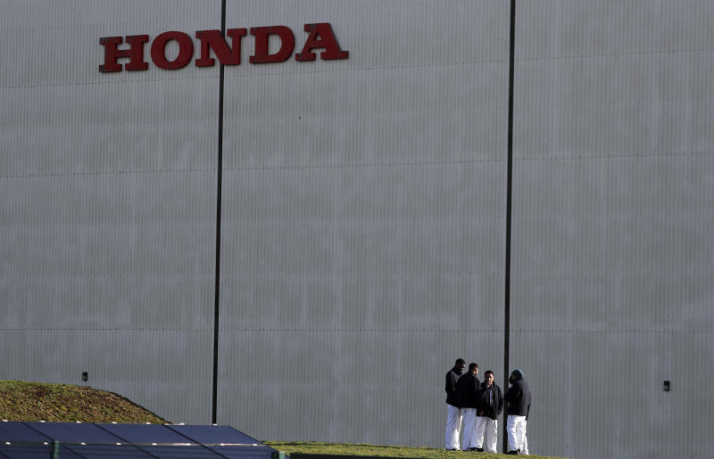 Employees gather as they have a break at the Honda car factory in Swindon, England, Tuesday, Feb. 19, 2019. The Japanese carmaker Honda announced Tuesday that its Swindon car plant in western England, will close with the potential loss of some 3,500 jobs. (AP Photo/Frank Augstein)