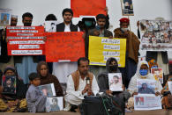 Nasrullah Baluch, center bottom, leader of the Voice of Baluch Missing Persons, speaks while people hold placards and portraits of their missing family members during a press conference in Islamabad, Pakistan, Saturday, Feb. 20, 2021. Dozens of relatives of Baluch missing persons, allegedly taken away by security agencies from restive Baluchistan province, Saturday ended their ten-day protest sleeping in the February cold near Pakistan parliament in capital Islamabad as minster for Human Rights assured their demand for recovery of loved ones would be taken seriously. (AP Photo/Anjum Naveed)