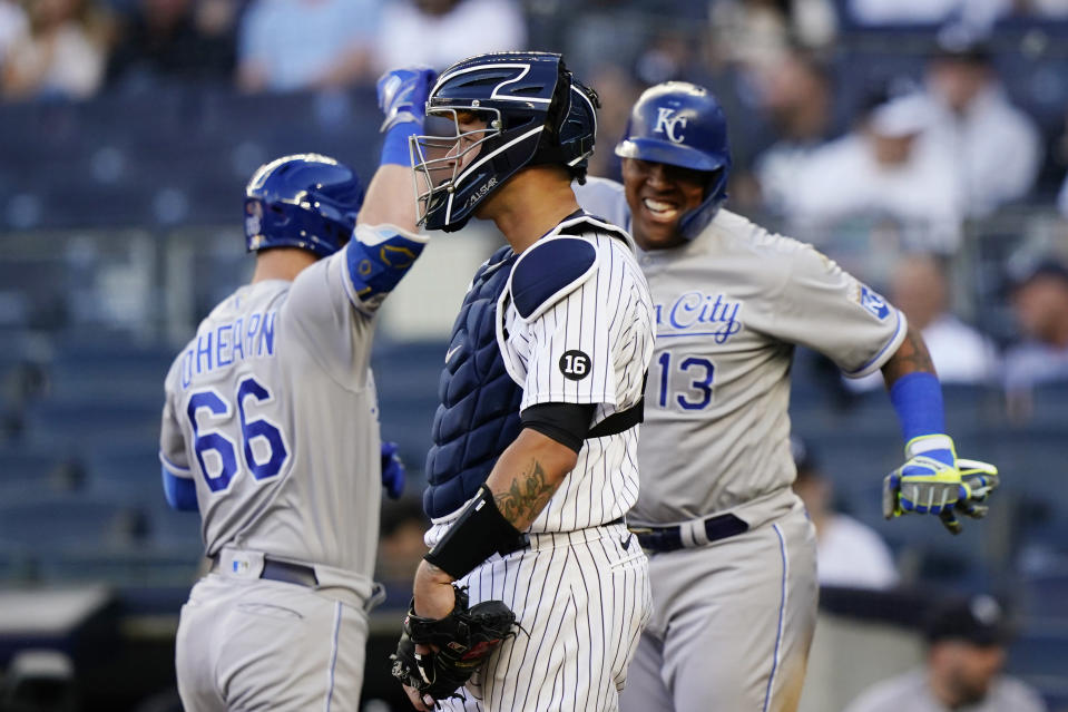 New York Yankees catcher Gary Sanchez, center, stares ahead as Kansas City Royals Ryan O'Hearn (66) and Salvador Perez (13) celebrate after O'Hearn hit a two-run, home run during the first inning of a baseball game, Wednesday, June 23, 2021, at Yankee Stadium in New York. (AP Photo/Kathy Willens)