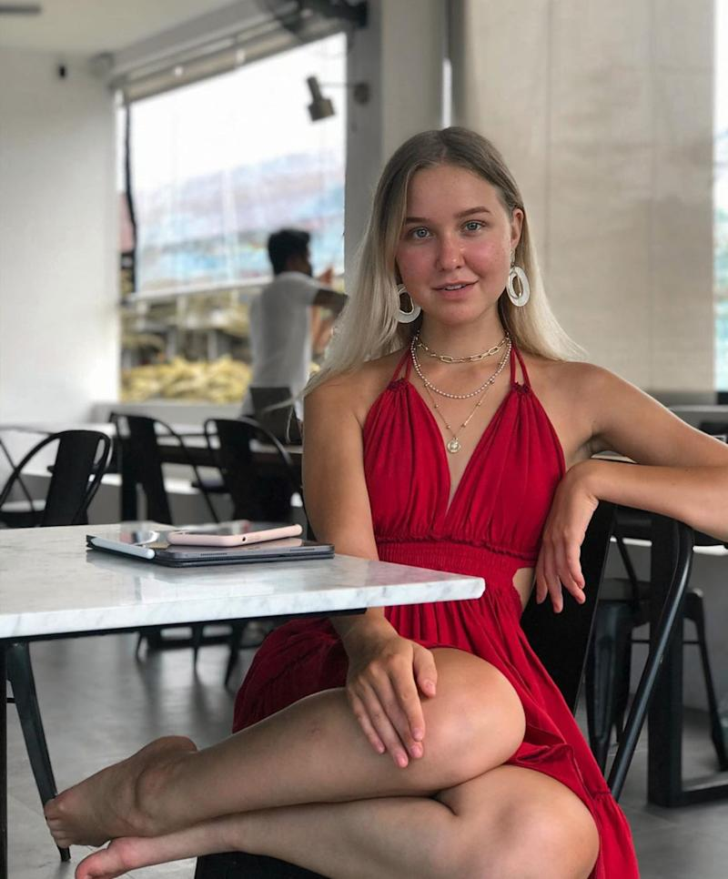 Anastasia Tropitsel is sitting in a cafe wearing a red dress.