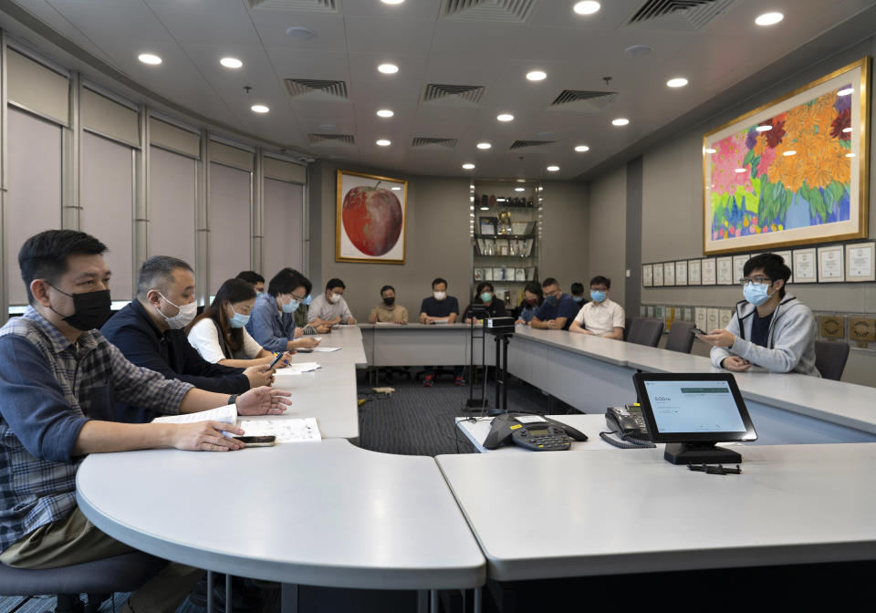 """Reporters attend an editorial meeting at the news room of Apple Daily Monday, April 26, 2021, in Hong Kong. A year ago, the pro-democracy Apple Daily newspaper published a front-page headline saying Hong Kong's governing principle of """"one country, two systems is dead."""" On Thursday, June 17, 2021, the newspaper was facing its greatest peril. Three top editors and two senior executives were arrested under Hong Kong's new national security law. (AP Photo/Vincent Yu)"""
