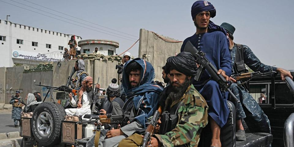 Taliban fighters holding guns on the back of a truck