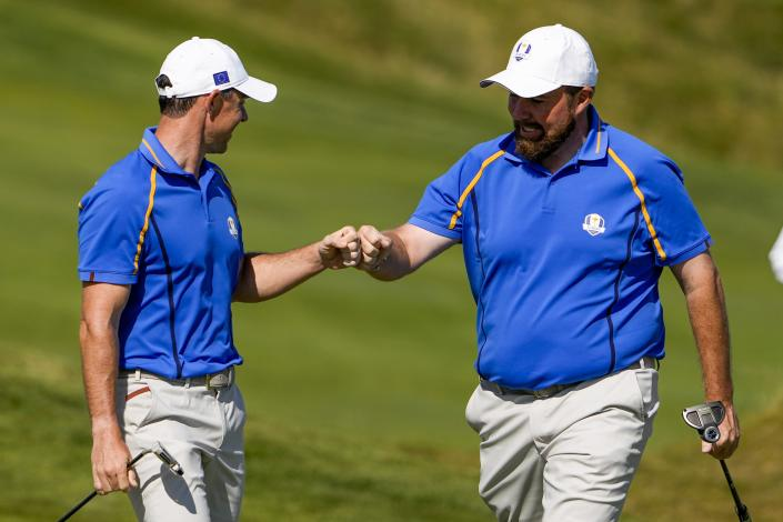 Team Europe's Shane Lowry is congratulated by Team Europe's Rory McIlroy after making a putt on the fourth hole during a four-ball match the Ryder Cup at the Whistling Straits Golf Course Friday, Sept. 24, 2021, in Sheboygan, Wis. (AP Photo/Jeff Roberson)
