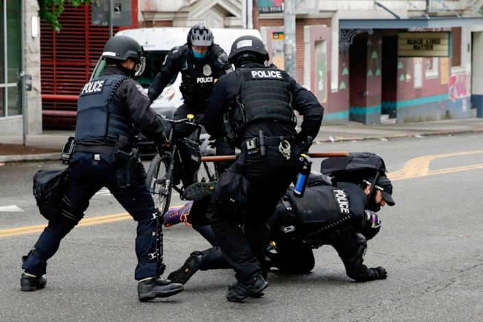 Police officers tackle a demonstrator to the floor at Seattle's CHOP zone, where Independent reporter Andrew Buncombe was arrested (AFP via Getty)