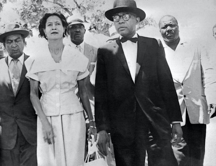 Black-and-white image of François Duvalier, in a suit, and his wife, in a dress, surrounded by watchful men