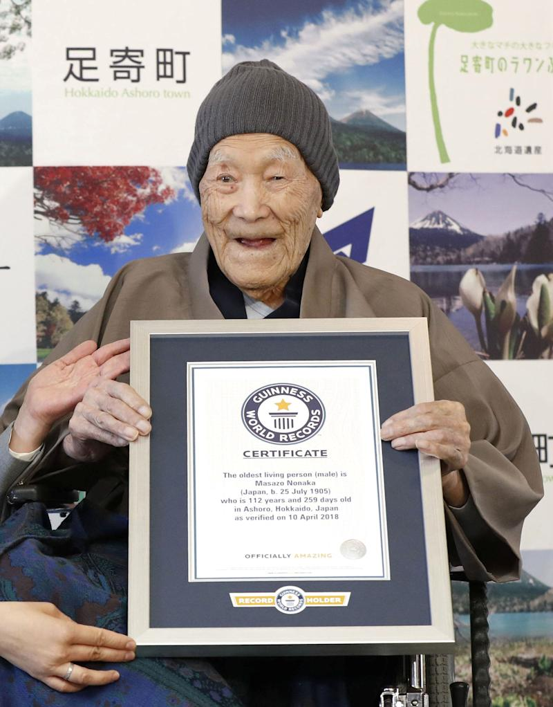 Masazo Nonaka, who was born 112 years and 259 days ago, receives a Guinness World Records certificate naming him the world's oldest man during a ceremony in Ashoro, on Japan's northern island of Hokkaido, on Tuesday.