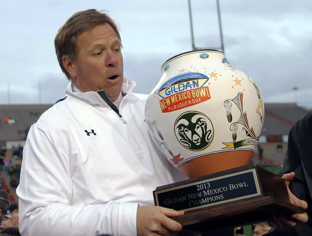 Colorado State head coach Jim McElwain accepts the winners trophy after the NCAA New Mexico Bowl college football game against Washington State, Saturday, Dec. 21, 2013, in Albuquerque, N.M. Colorado State won 48-45.(AP Photo/Matt York)