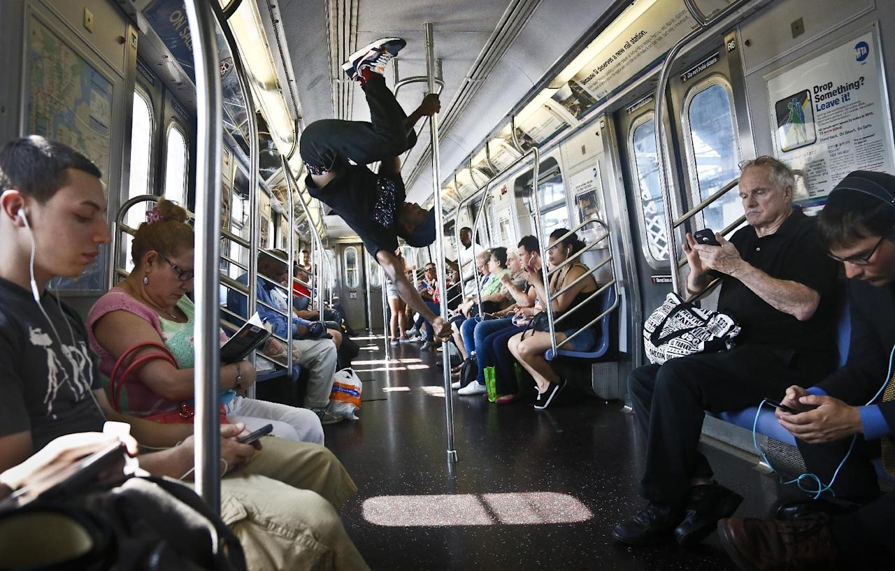 In this June 17, 2014 photo, Dashawn Martin, center, a member with the dance troupe W.A.F.F.L.E., which stands for We Are Family For Life Entertainment, performs on a subway, in New York. The subway acrobats said they're just out to entertain, make a living and put a little communal levity in New York's no-eye-contact commuting. (AP Photo/Bebeto Matthews)