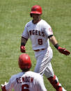 Los Angeles Angels' Anthony Rendon, bottom, congratulates Tommy La Stella after La Stella hit a solo home run during the first inning of a baseball game against the San Francisco Giants in Anaheim, Calif., Tuesday, Aug. 18, 2020. (AP Photo/Kelvin Kuo)