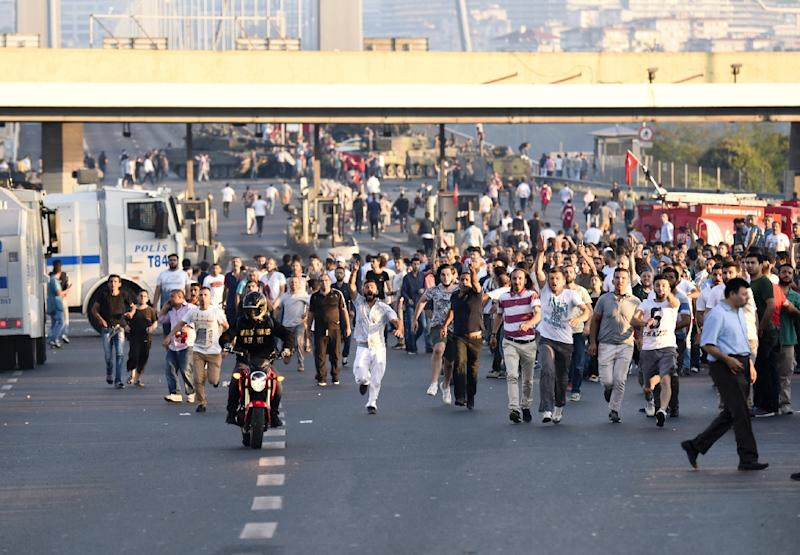 People run away from tanks after taking over military position on the Bosphorus bridge in Istanbul on July 16, 2016, following an attempt by discontented soldiers to seize power from President Recep Tayyip Erdogan