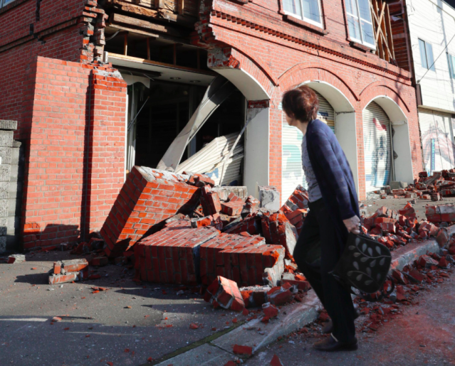 <em>A woman walks past a damaged building in Abira town, near Chitose, Hokkaido (AP)</em>