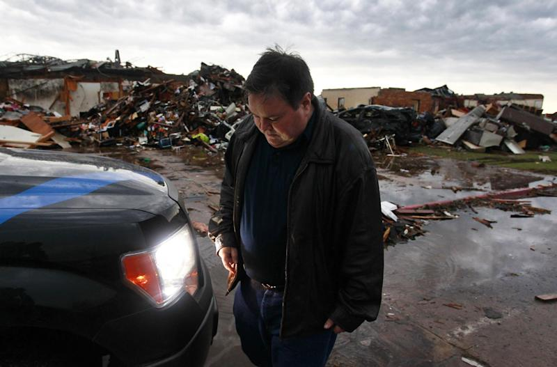 FILE - In this May 23, 2013 file photo, Moore, Okla. Mayor Glen Lewis gets back into his vehicle after visiting the rubble of Plaza Towers Elementary, where seven children were killed earlier in the week. In his 20 years as mayor of the Oklahoma City suburb, Lewis has already rebuilt his town twice, grappling with the aftermath of tornadoes so enormous the probability they strike is barely 2 percent. Yet Moore has been slammed by EF5 tornadoes, the largest on the rating scale, twice. (AP Photo/Brennan Linsley, File)