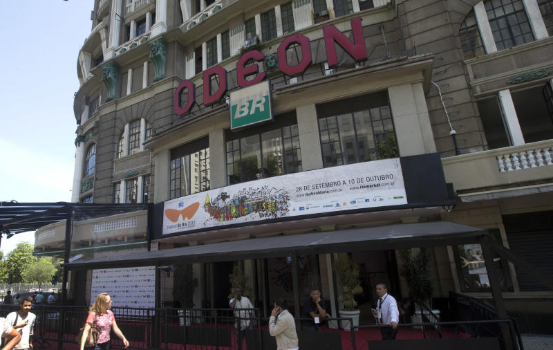 People walk in front the Odeon cinema, one of the cinemas participating on the Rio Film Festival in Rio de Janeiro, Brazil, Saturday, Sept. 28, 2013. Over the past decade, the federal government has invested more than $450 million in films, and many state and city governments also invest in movies made locally, provided they meet requirements that typically include hiring at least a certain number of local employees. (AP Photo/Silvia Izquierdo)