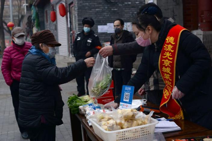 Woman wearing a face mask buys vegetables from a stall set up by a restaurant outside its outlet