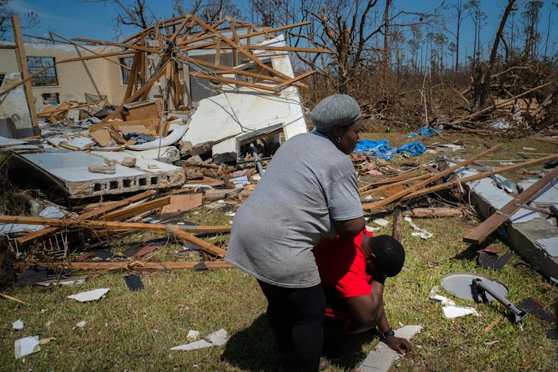 A woman comforts a man who cries after discovering his shattered house and not knowing anything about his eight missing relatives who lived there, High Rock, Grand Bahama, Bahamas, Thursday, Sept. 5, 2019. | Ramon Espinosa—AP